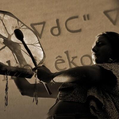 Une femme autochtone jouant du tambour; en arrière plan, du texte crie
