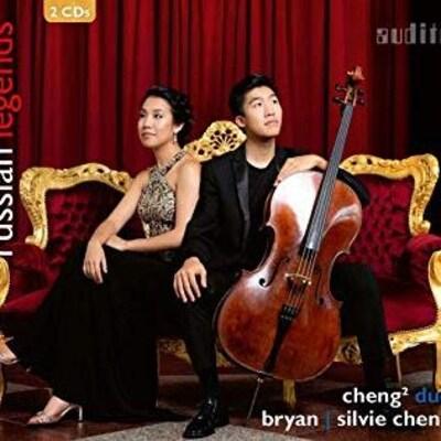 2 musiciens, 1 jeune homme et une jeune femme d'origine asiatique, assis en tenue de soirée sur un fauteuil de style baroque, rouge et or.