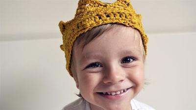 Un petit garçon porte une couronne.