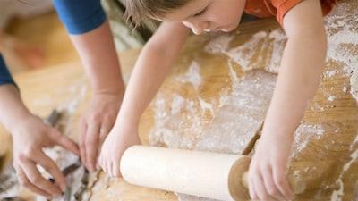 Un petit garçon utilise un rouleau à pâte.