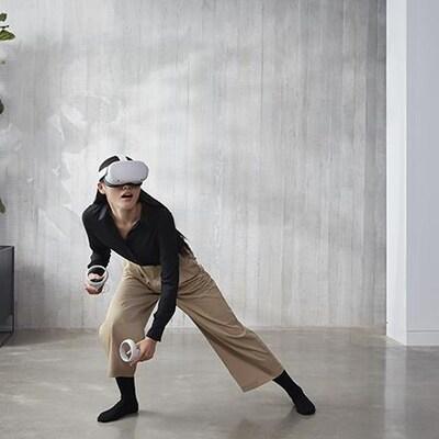 Une femme utilise un casque et des manettes de réalité virtuelle