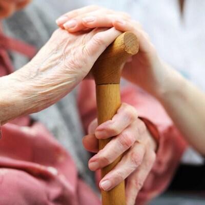 Gros plan sur les mains d'un aîné qui tient une canne.