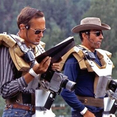 Deux hommes portent des équipements électroniques en étudiant une carte.