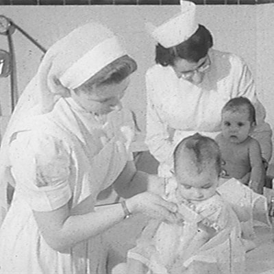 Image en noir et blanc montrant deux infirmières en train de faire la toilette de deux bébés.