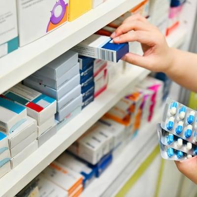 Une pharmacienne tient des médicaments.