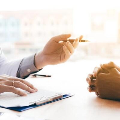 Un médecin tient un crayon en parlant à un patient.