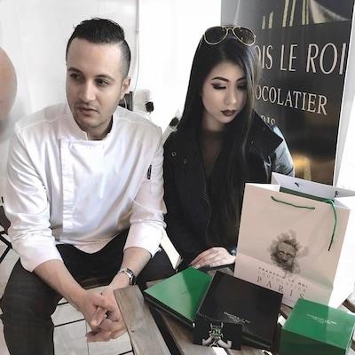 Le chocolatier et une jeune femme devant une affiche de sa boutique