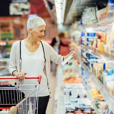 Femme regardant le tableau de valeur nutritive d'un aliment dans une épicerie