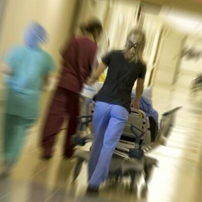 Des infirmières et la civière d'un patient le long d'un corridor d'hôpital.
