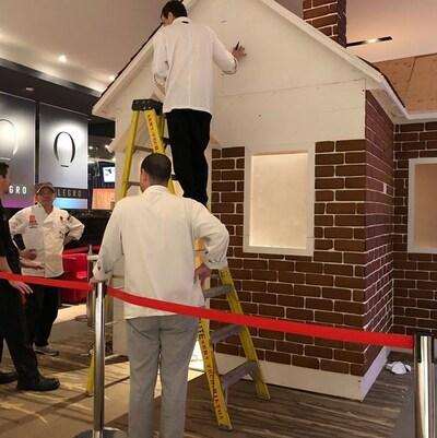 Des hommes travaillent à la construction d'une  maison en pain d'épices grandeur nature dans le hall de l'Hôtel Hilton Québec.