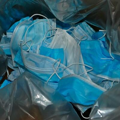 Des masques usagés sont réunis dans un petit amas.