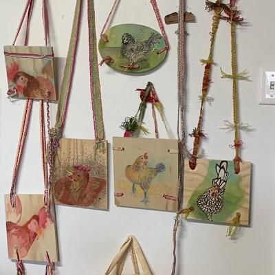Des poules dessinées sur de petits tableaux de bois.