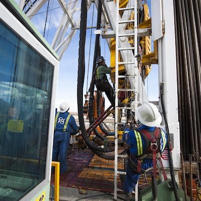 Plan serré de travailleurs s'activant sur le site d'un puits de gaz naturel en Colombie-Britannique.