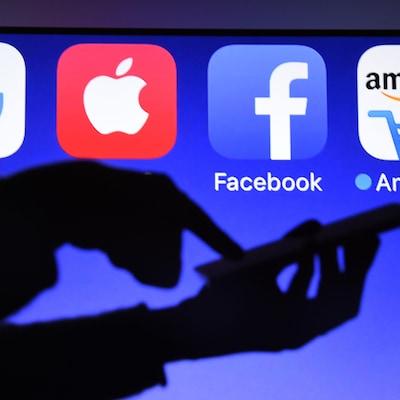 Une personne utilise un téléphone cellulaire devant un écran affichant les logos de Google, d'Apple, de Facebook et d'Amazon.