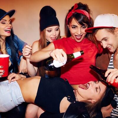 Quatre jeunes femmes et un jeune homme s'adonnent à un jeu avec de l'alcool.