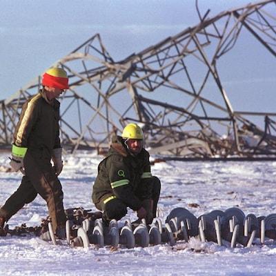 Deux hommes réparent un pylône détruit, en janvier 1998