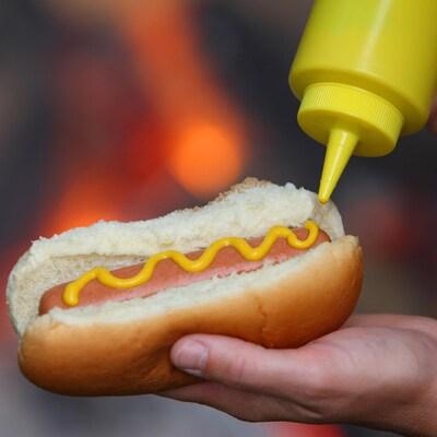 Une personne met de la moutarde dans un hot-dog.