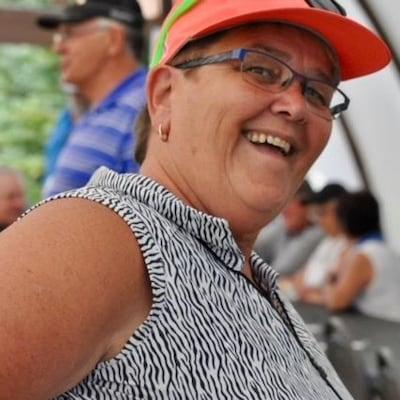 Mona Audet porte une casquette, des lunettes et fait un grand sourire.