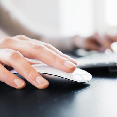 Une personne utilise une souris et un clavier d'ordinateur.