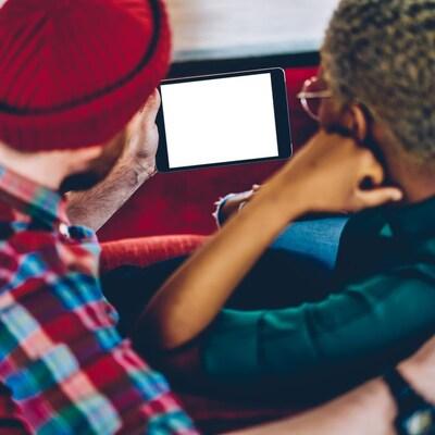 Photo d'un couple de dos qui regarde l'écran d'une tablette.