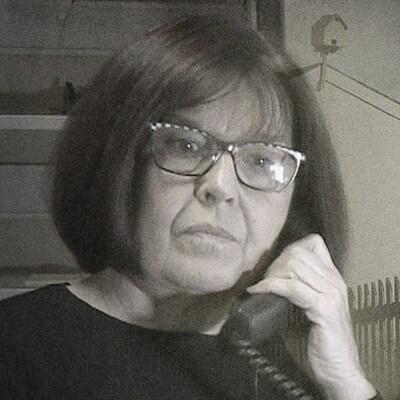 La journaliste Anne Panasuk, au téléphone, au côté d'une image de la communauté de Pakuashipi.