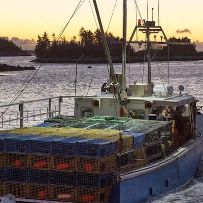 Un bateau de pêche au homard quitte un port