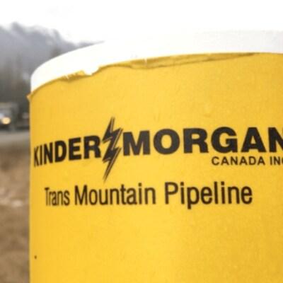 La photo montre une affiche liée au projet de pipeline Trans Mountain près d'une route.