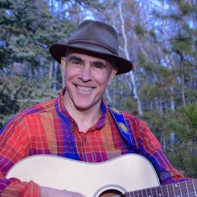 Un homme tient une guitare et sourit à la caméra.