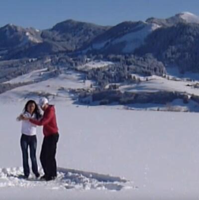 Un couple danse la salsa dans la neige sur fond de montagnes enneigées