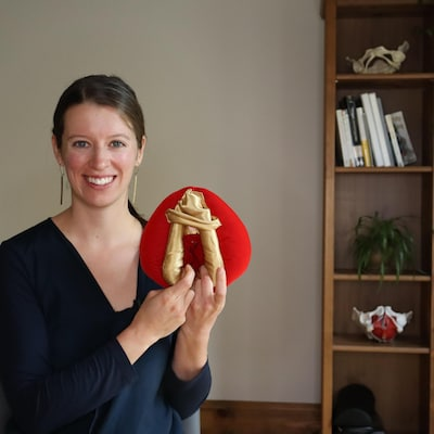 une femme tenant une maquette d'une vulve.
