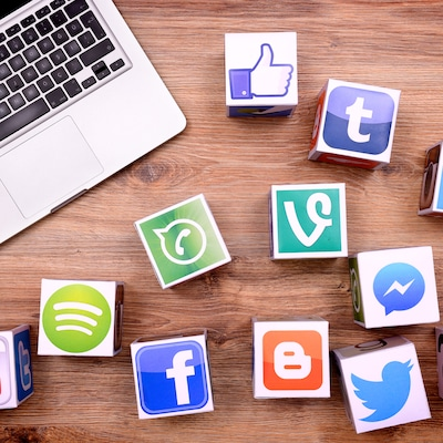 Photo d'un ordinateur et de cubes avec les symboles des réseaux sociaux. Les entreprises privées contrôlent à elles seules les volumes de données nécessaires à la recherche dans le domaine des algorithmes.