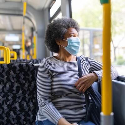 Une femme assise dans un bus porte un masque.
