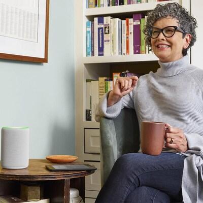 Une femme assise dans un fauteuil écoute quelque chose diffusé sur le  haut-parleur Amazon Echo déposé sur une table.