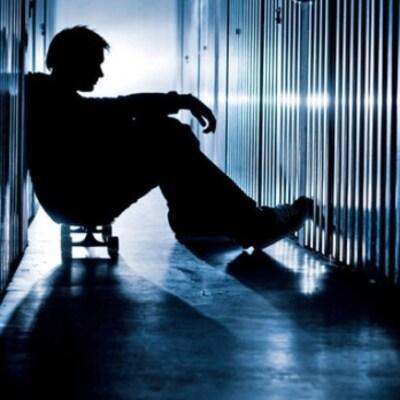 Un jeune homme assis entre des casiers souffre de santé mentale