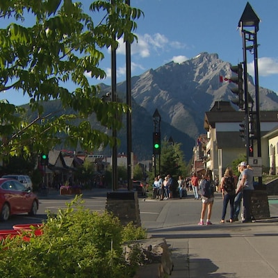 Quelques personnes attendant que le feu de circulation change pour traverser une intersection à Banff.