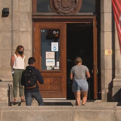 La porte d'entrée du cégep de Rimouski à côté de laquelle se tient une femme qui regardent deux étudiants monter les marches pour entrer dans l'établissement.