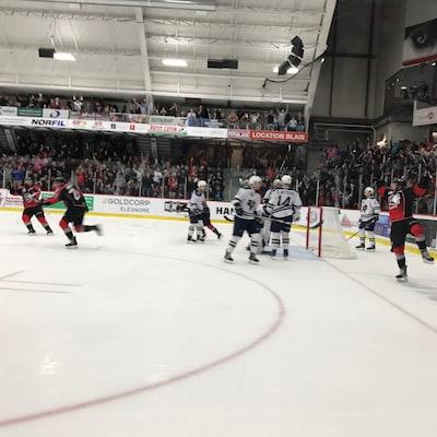 Des joueurs célèbrent sur la patinoire à la suite d'un but.