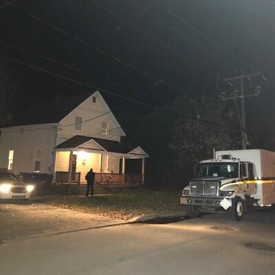Des véhicules du Service de police de la Ville de Gatineau et de la Sureté du Québec autour de la résidence.