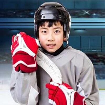 Un jeune garçon habillé en habit de hockey.