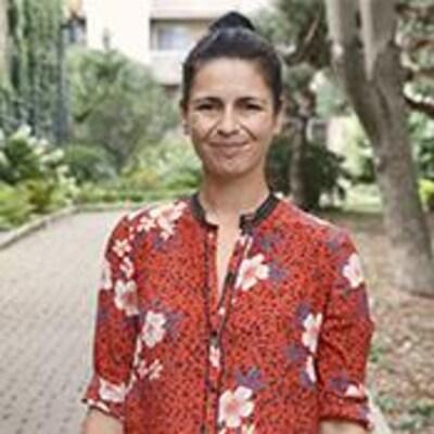 Helen Faradji, vêtue d'une robe fleurie, sourit à la caméra.