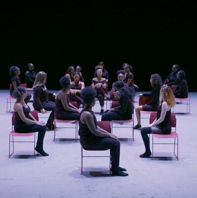 Les filles exécutent leur chorégraphie sur des chaises rouges. Elles sont toutes habillées en noir.