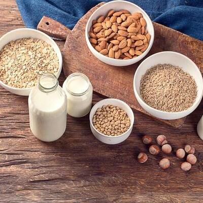 Sur une table de bois, des flocons d'avoine, du riz, des amandes et des pois sont disposés. À côté des semences, on trouve différentes pintes de lait qui on suppose, sont créées à base de ces ingrédients.