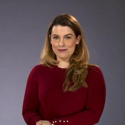 L'animatrice pose sur un fond gris. Elle a un chandail à manches longues de couleur rouge.