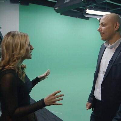 L'animatrice pose des questions à son invité. Le mur est peint en vert.