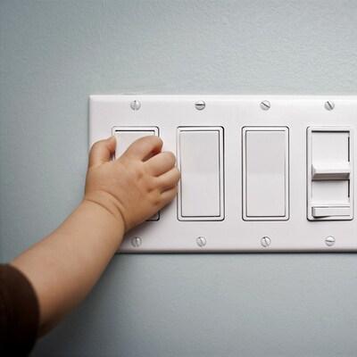 Une petite main d'enfant est tendue vers l'interrupteur, qui permettra d'éteindre la lumière.