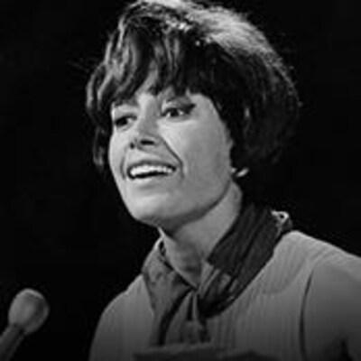 Pauline Julien, en noir et blanc, parle dans un micro.