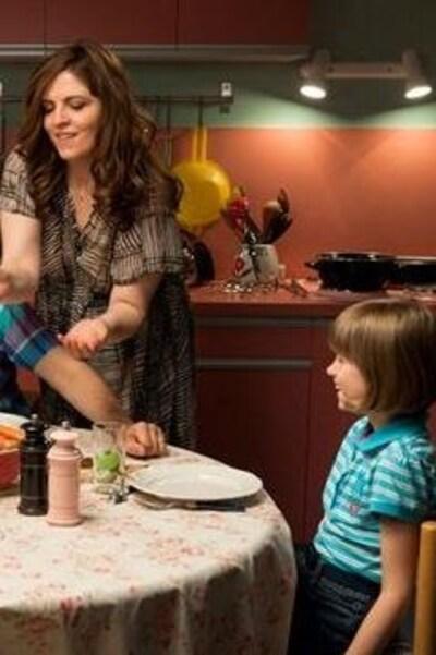 Une famille assise à table, dans une cuisine.