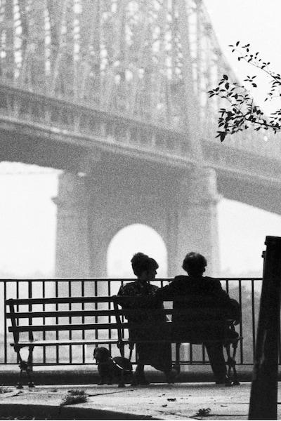 En noir et blanc, un homme et une femme de dos, assis sur un banc, sous le pont de Brooklyn, à New York.