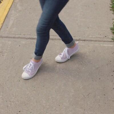 Gros plan sur les pieds d'Alice qui danse sur un trottoir.