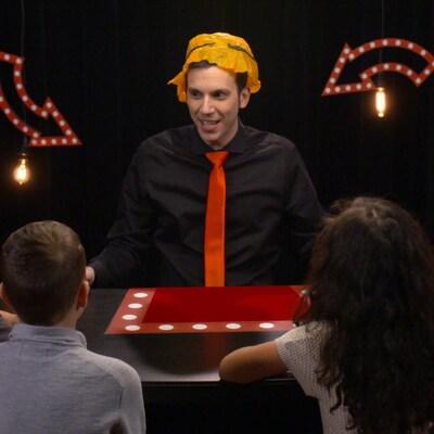 Devant 4 enfants, Daniel Coutu s'est mis un papier de soie orange sur la tête comme chapeau.